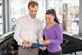 Happy couple with car key in dealership after buying an automobile a Royalty Free Stock Image