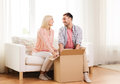 Happy couple with cardboard box or parcel at home people delivery shipping and postal service concept opening Royalty Free Stock Photos