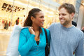 Happy couple carrying bags in shopping mall smiling at each other Stock Photos
