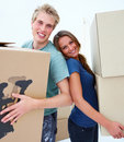 Happy couple carrying boxes moving house Royalty Free Stock Photography