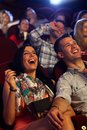Happy couple at the cinema watching comedy in movie theater laughing Stock Photos