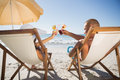 Happy couple clinking their glasses while relaxing on their deck the beach chairs Royalty Free Stock Photos