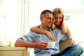 Happy couple with coffee, reading the news Royalty Free Stock Photo