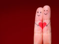 Happy couple concept two fingers in love with painted smile smiley faces and heart over red background Stock Photos