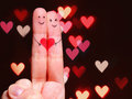 Happy couple concept two fingers in love with painted smiley faces and heart over bokeh background Stock Photos