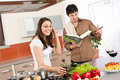 Happy couple cook in kitchen with cookbook Royalty Free Stock Photo