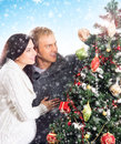 A happy couple decorating the christmas tree young and pregnant women and father image is taken on light blue and snowy background Stock Images