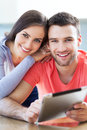 Happy couple with digital tablet smiling Royalty Free Stock Image
