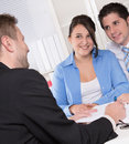 Happy couple discussing future financial plans with consultant at office meeting Royalty Free Stock Images
