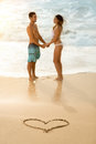 Happy couple with draw heart on sandy beach Royalty Free Stock Photo