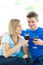 Happy couple drinking wine together in living-room Stock Image