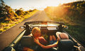 Happy couple driving in convertible young along country road at sunset Stock Image
