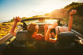 Happy couple driving in convertible young carefree along country road at sunset Royalty Free Stock Photo