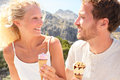 Happy couple eating ice cream cone outdoors enjoying nature lifestyle fresh young romantic enjoying summer looking at Stock Images