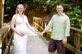 Happy couple expecting a baby young holding hands outside on wooden bridge Royalty Free Stock Image