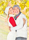 Happy couple in fall under leaves of a broad leaved lime Stock Images