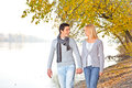 Happy couple in fall under leaves on the river Royalty Free Stock Image