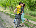 Happy couple with flowers & bicycle kissing Royalty Free Stock Image