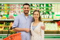 Happy couple with food basket at grocery store Royalty Free Stock Photo