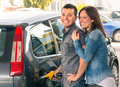 Happy couple at fuel station pumping gasoline at gas pump portrait of young men and women of men filling modern car Royalty Free Stock Image