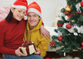 Happy couple with gift sitting near Christmas tree Stock Photos