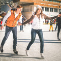 Happy couple, girls and boy ice skating outdoor at rink Royalty Free Stock Photo