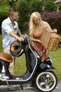 Happy couple going for outdoor picnic with scooter casual caucasian elegant attractive smiling blonde woman basket Royalty Free Stock Photography