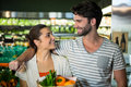 Happy couple with a grocery bag smiling at each other in organic section Royalty Free Stock Photo