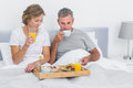 Happy couple having breakfast in bed together at home bedroom Stock Photography
