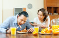 Happy couple having breakfast after night together with scrambled eggs and oranges in morning Stock Photography