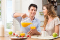 Happy couple having breakfast portrait of man pouring juice in glass for young woman Royalty Free Stock Images