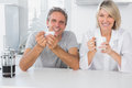Happy couple having coffee in the morning kitchen smiling at camera Royalty Free Stock Photos