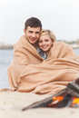 Happy couple having fun around bonfire lovers sitting under blanket and warming near fire Stock Photography