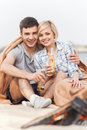 Happy couple having fun around bonfire two friends sitting under blanket and warming near fire Stock Photos