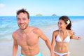 Happy couple having fun on beach vacation during summer holiday multiracial fit running together holding hands laughing in Stock Photos