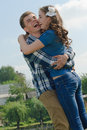 Happy couple having fun embracing over blue sky background teenage boy and girl Stock Image