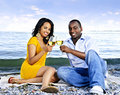Happy couple having wine on beach Stock Photo