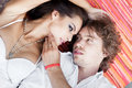 Happy couple with heads together on the floor portrait of a young men and sensual brunette outdoor portrait in classic dress Royalty Free Stock Photography