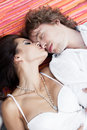 Happy couple with heads together on the floor portrait of a young men and sensual brunette outdoor portrait outdoors Stock Images