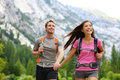 Happy couple of hikers hiking holding hands joyful cheerful and fresh young active multiracial couple in outdoor activity hike in Royalty Free Stock Photos