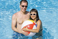 Happy Couple Holding Beach Ball in a Swimming Pool Stock Image