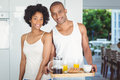 Happy couple holding breakfast tray in the kitchen at home Stock Photography