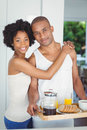 Happy couple holding breakfast tray in the kitchen at home Royalty Free Stock Image
