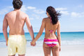 Happy couple holding hands and looking at the sea Royalty Free Stock Photo