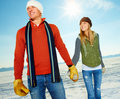 Happy couple holding hands out on the snow Royalty Free Stock Photo