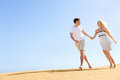 Happy couple holding hands running having fun in playful and romantic relationship under sun and blue sky in desert two young Stock Image