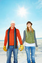 Happy couple holding hands and standing on snow Royalty Free Stock Image