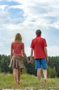 Happy couple holding hands young in love walking in the park Royalty Free Stock Image