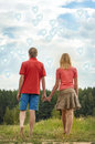 Happy couple holding hands young in love walking in the park Stock Photography
