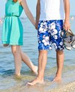 Happy couple on holiday walking holding hands on seashore young summer outdoors background Stock Photography